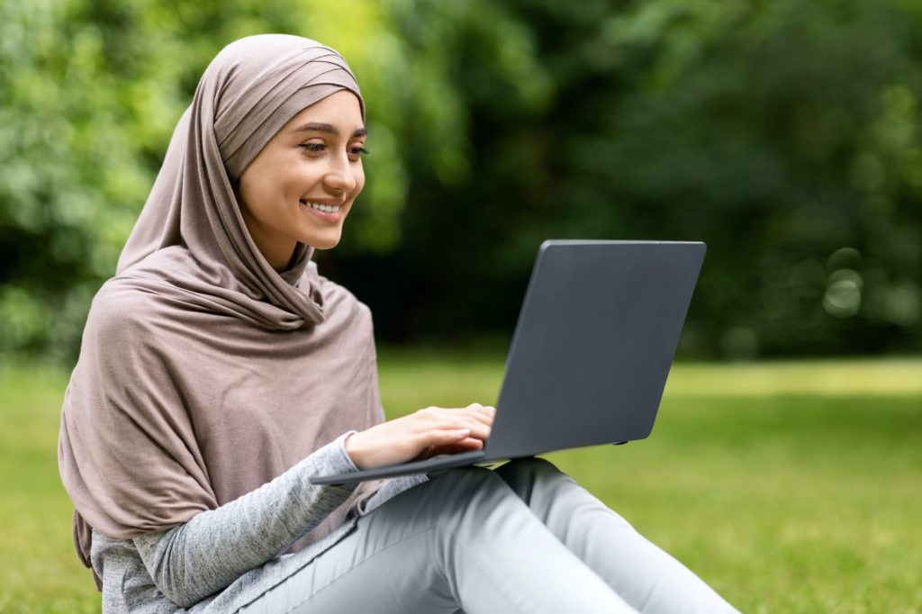 Smiling pretty muslim girl using laptop while resting at park