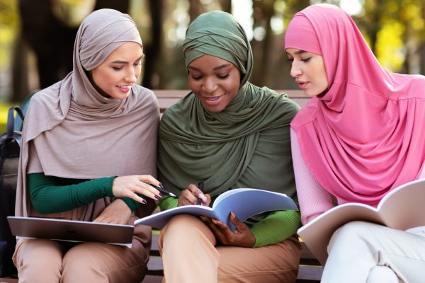 Three Female Arab Students Learning Together Reading Books Sitting Outdoors